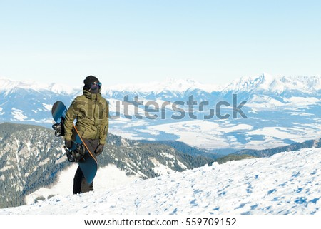 Snowboarder holding his board in hand and climbing to the top of a mountain