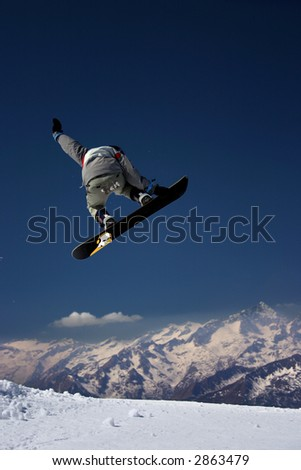 Snowboarder in grey jacket juping high - winter mountain action scene