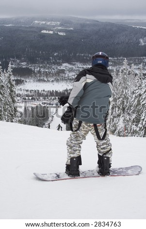 Snowboarder in grey outfit at the start of the downhill slope. - stock photo