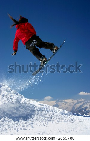 Snowboarder in red jacket jumping high - winter mountain action scene