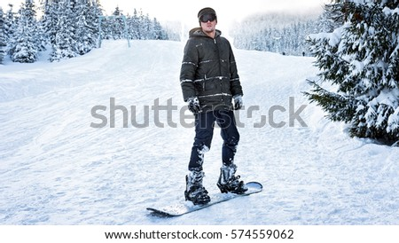 Snowboarder in ski glasses stands on a snowboard in the winter woods on the slopes among the snow-covered firs