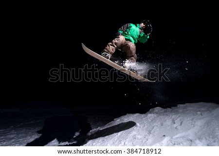 Snowboarder jumping at night