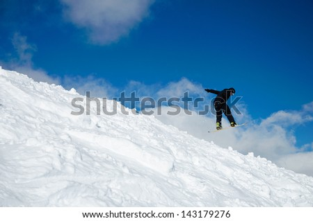 Snowboarder jumping from a natural drop into a lot of snow
