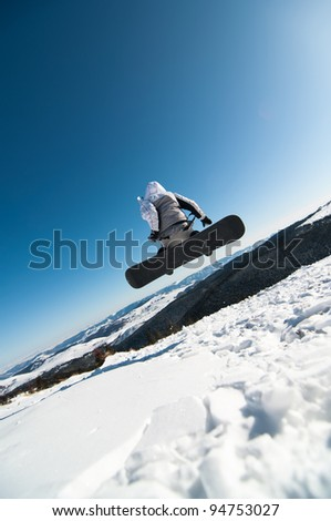 Snowboarder jumping in the snow with clear sky background - stock photo
