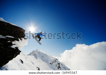 Snowboarder jumping through air after rock drop - stock photo