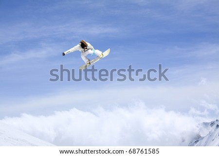 Snowboarder jumping through air with sky in background