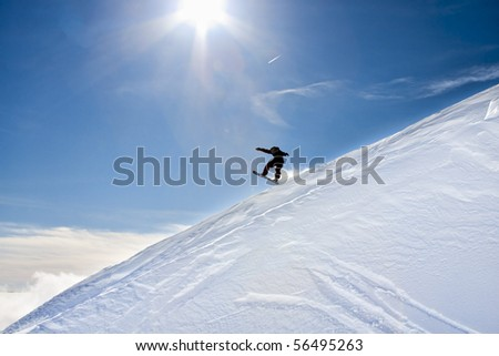 Snowboarder jumps down an incline of the Mountain on a bright, sunny day with blue skies. - stock photo