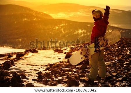 Snowboarder on mountain background sunset. - stock photo