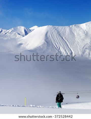 Snowboarder on off-piste slope and mountains in mist. Caucasus Mountains, Georgia, region Gudauri. - stock photo