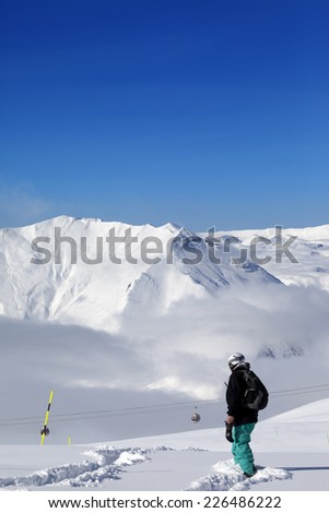 Snowboarder on off-piste slope with new fallen snow at nice day. Caucasus Mountains, Georgia, ski resort Gudauri.