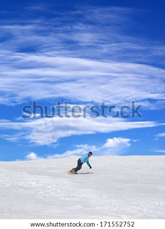 Snowboarder on ski slope and blue sky with clouds at nice day - stock photo