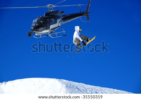 snowboarder performs a high jump while being filmed from a helicopter equipped with a front mounted steady cam.