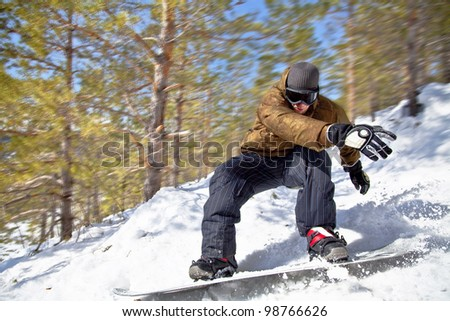 Snowboarder rides at high speed through the winter forest. Close-up. Motion Blur. - stock photo
