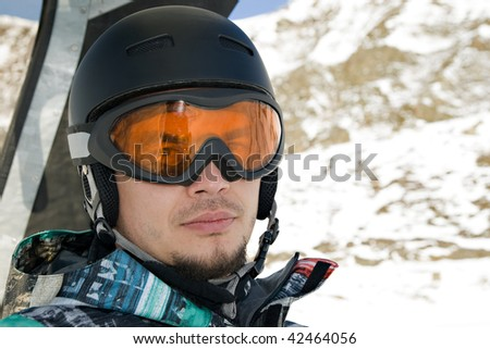 Snowboarder riding a chairlift. Front view head shot