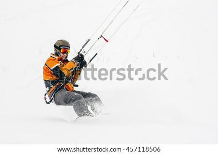 Snowboarder riding a kite