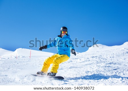 Snowboarder sliding down the hill - stock photo