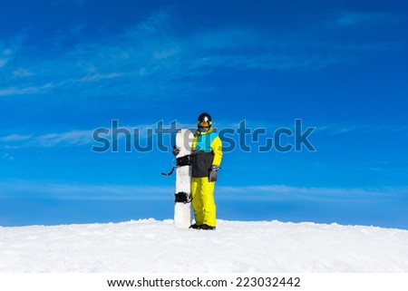 snowboarder standing hold snowboard, snow mountain slope copy space blue sky - stock photo