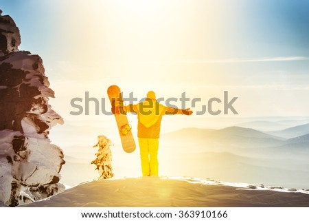Snowboarder stands on background of valley and holds snowboard in raised hands. Sheregesh resort, Siberia, Russia - stock photo