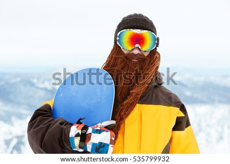 Snowboarder with funny beard holds snowboard. Sheregesh ski resort. Fun