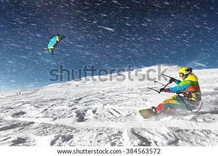 Snowboarder with kite on free ride. Sheregesh resort, Siberia, Russia - stock photo