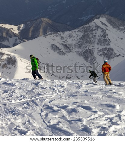 Snowboarders and skier on off-piste slope in sun evening. Caucasus Mountains, Georgia. - stock photo