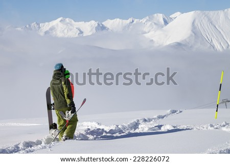 Snowboarders on off-piste slope with new fallen snow. Caucasus Mountains, Georgia, ski resort Gudauri.