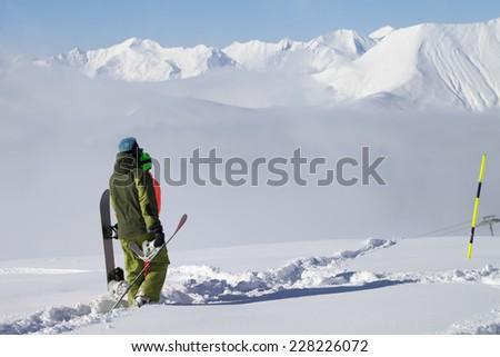 Snowboarders on off-piste slope with new fallen snow. Caucasus Mountains, Georgia, ski resort Gudauri. - stock photo