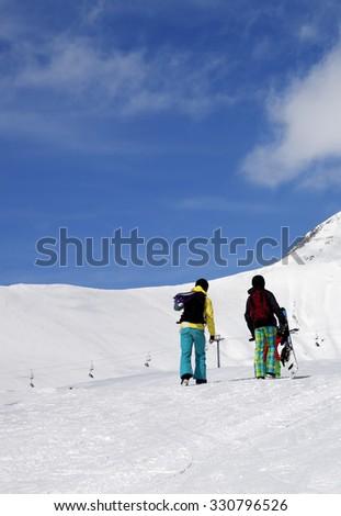 Snowboarders on slope at sun nice day. Caucasus Mountains, Georgia, ski resort Gudauri. - stock photo