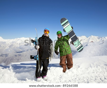 Snowboarders on top of a mountain overlooking a beautiful panorama - stock photo