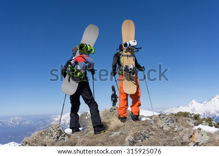 Snowboarders standing on top of a snowy mountain - stock photo