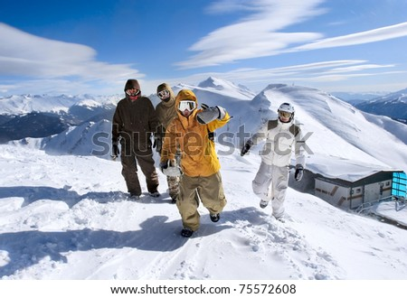 Snowboarders walking along the ridge of the mountains - stock photo
