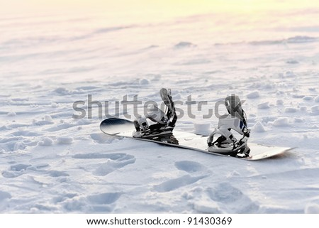 Snowboarding in the snow at sunset - stock photo