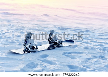 Snowboarding in the snow at sunset, with fastening