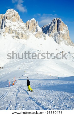 Snowborder going down the slope at Val Di Fassa ski resort in Italy - stock photo