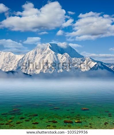 snowbound mountains and emerald sea - stock photo