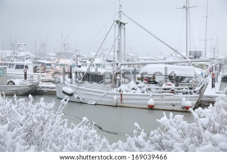 Snowbound Steveston Harbor, Richmond, British Columbia. A lone fishboat tied to the dock waiting out a winter snowstorm. Steveston, British Columbia, Canada. - stock photo