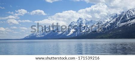 Snowcapped Grand Teton mountain range viewed above Lewis Lake - stock photo
