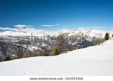 "Snowcapped high mountain peaks in the italian french alpine arc in the ""Via Lattea"" ski resort, Torino, Italy. Massif des Ecrins (over 4000 m) and M. Chaberton (3131 m) in the background. - stock photo"