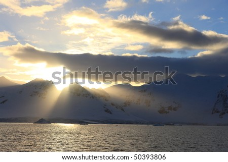 Snowcapped Land in sunlight Antarctica seen from a sailing boat - stock photo