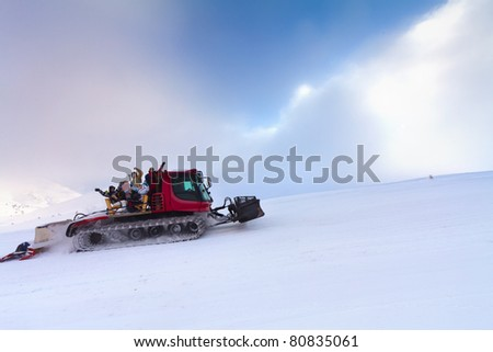 Snowcat with people going up the hill. - stock photo