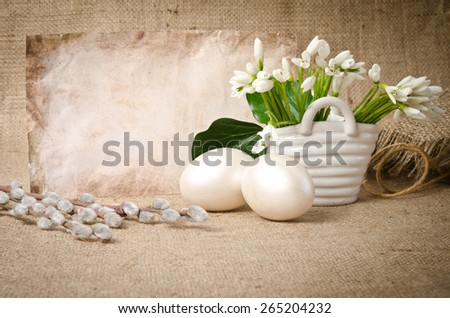Snowdrop with  eggs for easter near empty blank for text on sacking background - stock photo