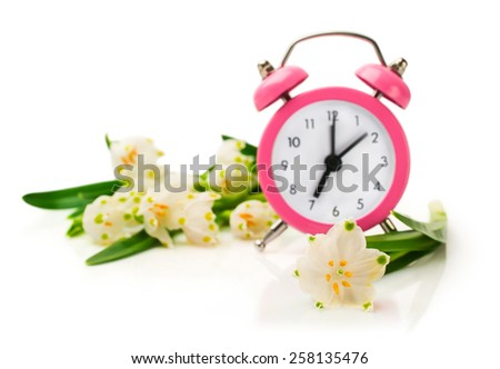 Snowdrops and pink alarm clock isolated on white - stock photo