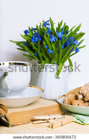snowdrops in a vase, a cup of tea and biscotti on the table - stock photo