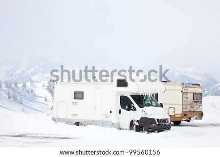 Snowed motorhomes at winter mountains - stock photo