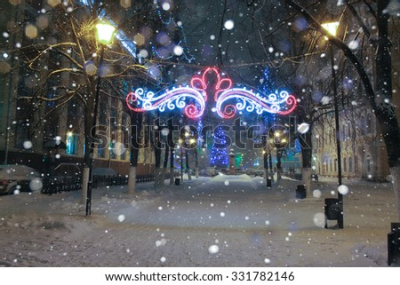 Snowfall in the park decorated for Christmas. Night shot at slow shutter speeds. Christmas lights, snow-covered park. City alley, street, park. background, copy space. - stock photo