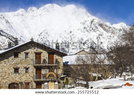 Snowfall view in the ski resort  Cerler, Huesca, in the Pyrenees of Aragon, Spain. View of a rustic house and the snowy mountains in a sunny and blue sky day.