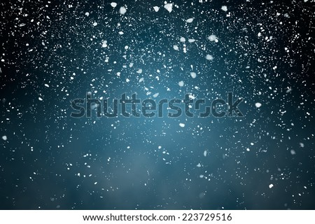 Snowfall with Blue Background - Fluffy snowflakes falling in front of a blue background with vignette - stock photo