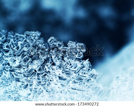 Snowflake ice crystals macro closeup dark blue background - stock photo