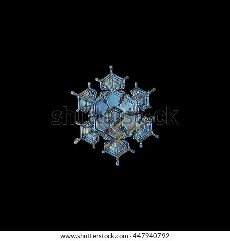 Snowflake isolated on black background: macro photo of real snow crystal, captured on glass with LED back light. This is small stellar dendrite snowflake with beautiful short arms and glossy surface. - stock photo