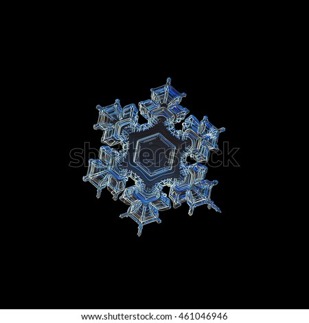Snowflake isolated on black background. This is macro photo of real snow crystal with complex short arms and simple central hexagon, version in dark blue colors.